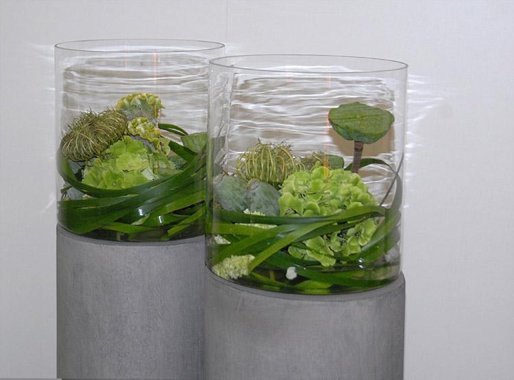 Glas mit Gräsern auf Steinsäule