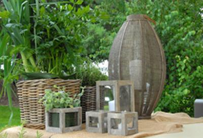 Arrangement: Vase, Windlicht, Korb und Holz